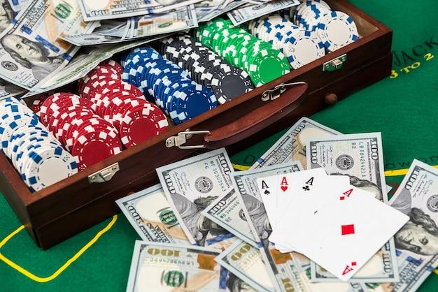 Fichas de pôquer no caso em uma mesa de jogo com cartas e dólares.