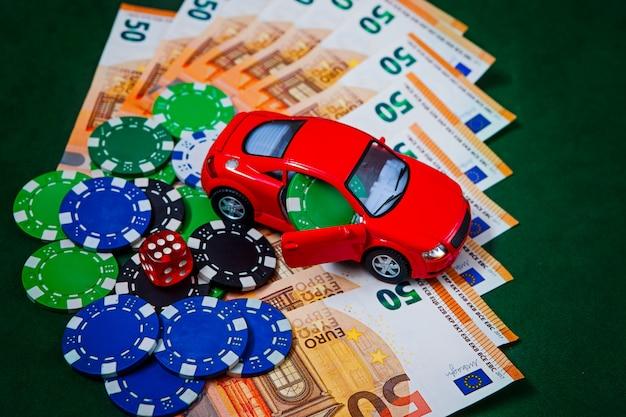 Fichas, dinheiro, euros em uma mesa de pôquer verde com uma máquina de escrever audi em vermelho.