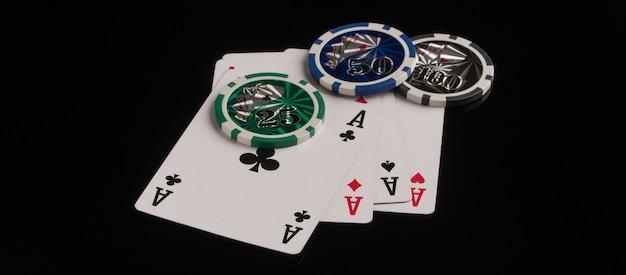 Fichas e cartas de pôquer em um fundo preto o conceito de jogos de azar e entretenimento
