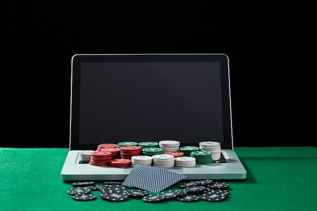 Fichas e cartões de cassino no teclado do notebook na mesa verde