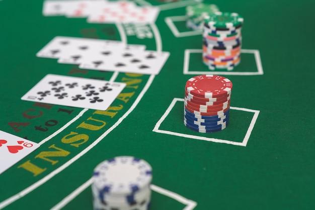 Fichas e cartões de poker na mão na mesa verde