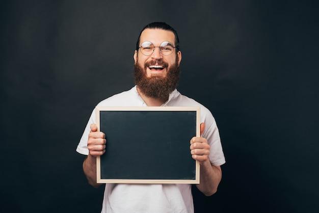 Fico feliz em anunciar isso. homem sorridente está segurando um quadro negro.
