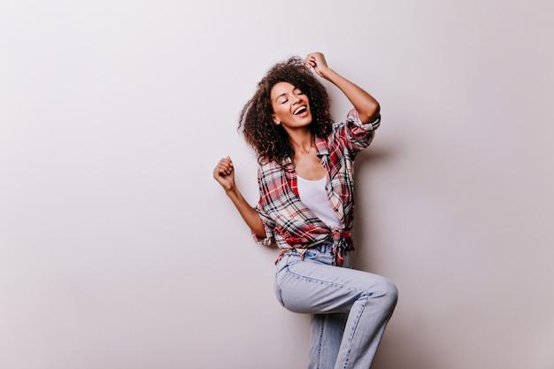 Fico feliz em dançar mulher africana rindo. menina bonita em jeans vintage relaxando em branco.