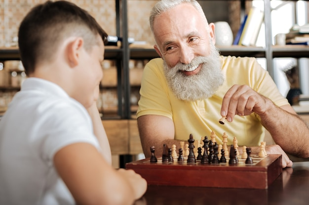 Fico feliz em jogar. um homem idoso e bonito com uma barba grisalha segurando um peão na mão e dando o próximo passo em um jogo de xadrez com seu amado neto