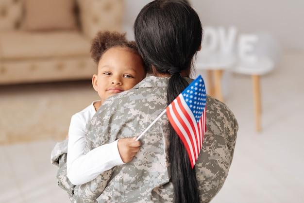 Fico feliz em tê-lo aqui. linda garota adorável abraçando a mãe com força enquanto a cumprimentava em casa e segurando uma bandeira na mão