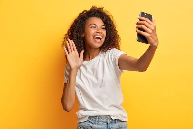 Fico feliz, mulher feliz, de pele escura, com penteado afro, segura o celular moderno na frente do rosto, acena com a palma da mão na câmera, faz videochamada, vestida com roupa casual