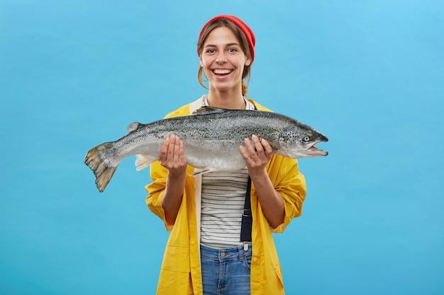 Fico feliz, mulher pescadora com anoraque amarelo segurando um peixe enorme, regozijando-se em pegá-lo, demonstrando seu trabalho em pé sobre a parede azul. pessoas, hobby, recreação e pesca