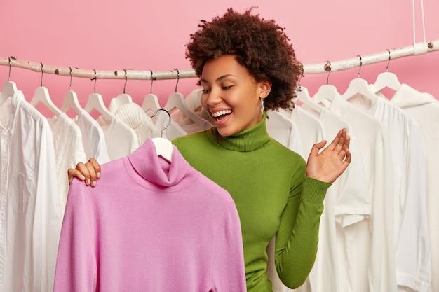 Fico feliz por uma jovem afro feliz em encontrar um macacão, segura uma blusa de gola alta roxa no cabide, escolhe roupas para a festa, faz compras na butique, mantém a palma da mão levantada