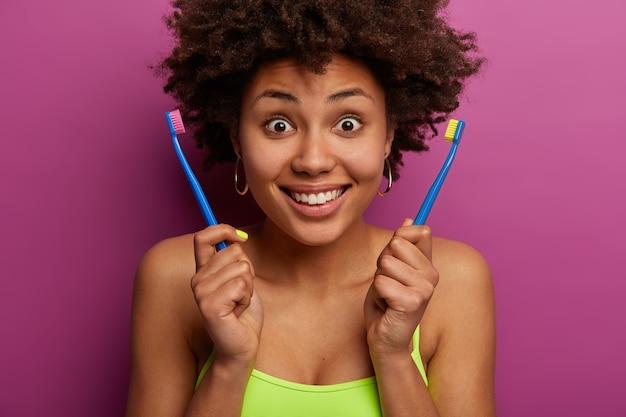 Fico surpreso com uma mulher afro-americana segurando duas escovas de dente