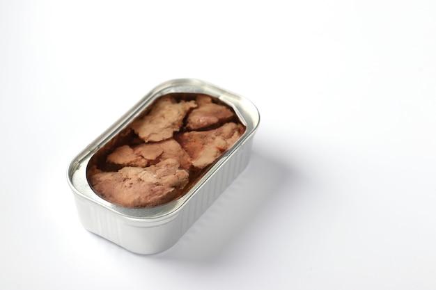 Fígado de bacalhau em uma jarra de ferro em um fundo branco com lugar para texto. formato horizontal