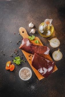 Fígado de bovino cru com especiarias, ervas e legumes, mesa enferrujada escura cópia espaço vista superior