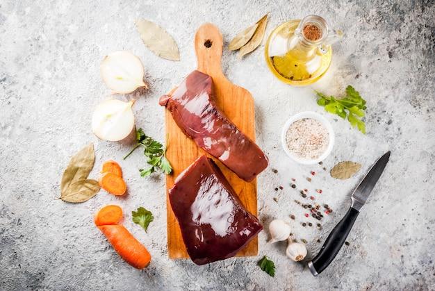 Fígado de bovino cru com especiarias, ervas e legumes, vista de mesa de pedra cinza