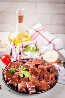 Fígado de bovino cru fatiado com especiarias, ervas e legumes, mesa de mármore branco