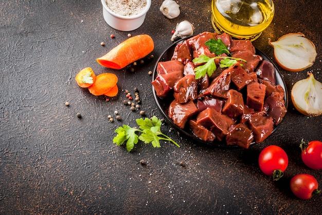 Fígado de bovino cru fatiado com especiarias ervas e legumes mesa enferrujada escura