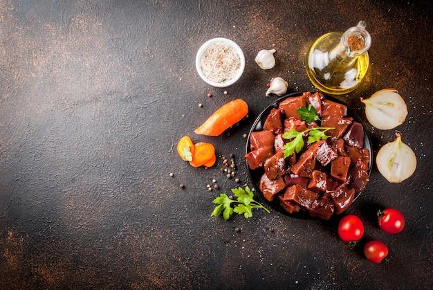 Fígado de bovino cru fatiado com especiarias, ervas e legumes, vista de mesa enferrujada escura