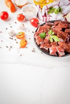 Fígado de bovino cru fatiado com especiarias, ervas e legumes