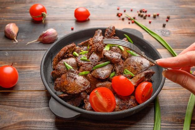 Fígado de frango caseiro frito com molho de soja, tomate, cebola e especiarias na mesa de madeira. a mão de uma mulher segura um garfo com um pedaço espetado