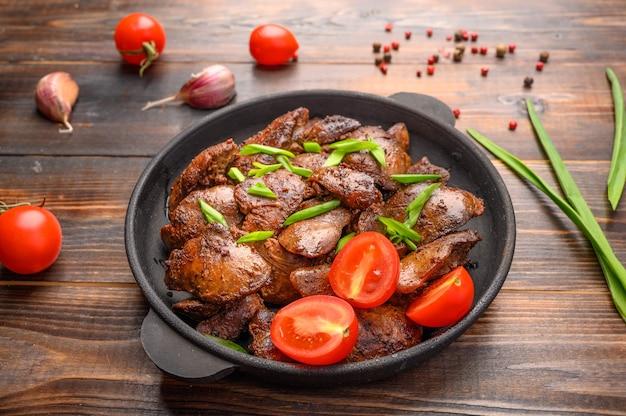 Fígado de frango caseiro frito com molho de soja, tomate, cebola e especiarias na mesa de madeira. fechar-se. foco seletivo. comida saudável.