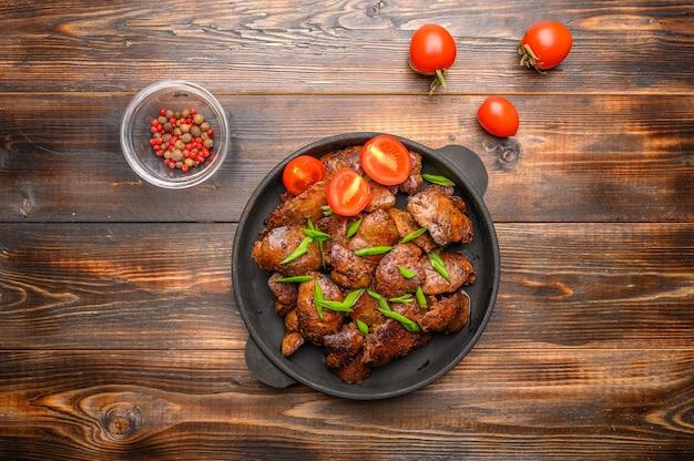 Fígado de frango caseiro frito com molho de soja, tomate, cebola e especiarias na mesa de madeira. fechar-se. foco seletivo.