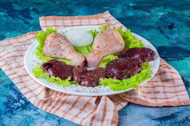 Fígado de frango, folhas de alface e coxinha de frango em um prato sobre o pano de prato
