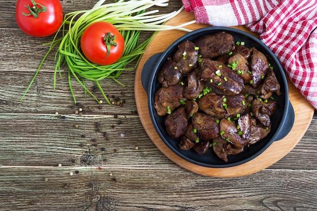 Fígado de frango frito com cebolinha jovem em uma frigideira de ferro fundido. saboroso prato saudável. vista do topo