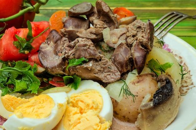 Fígado de frango frito, tomates desbastados com verdes e ovos cozidos.