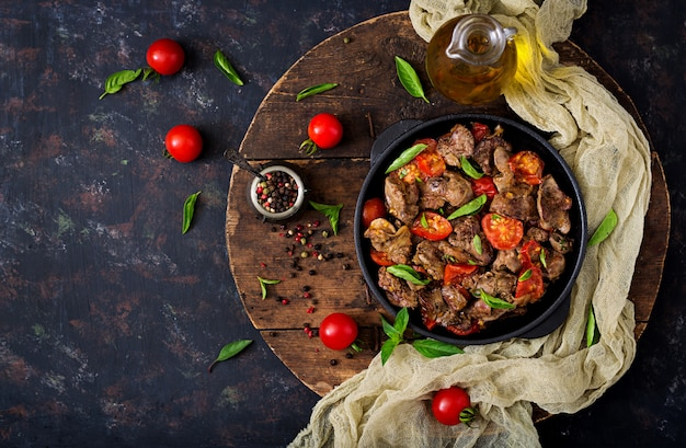 Fígado de galinha (miudezas) com cebola e tomate em uma frigideira em armênio. postura plana. vista do topo