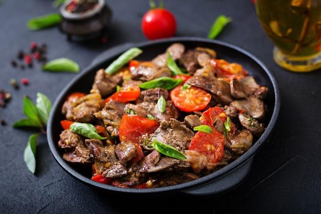 Fígado de galinha (miudezas) com cebola e tomate em uma frigideira em armênio