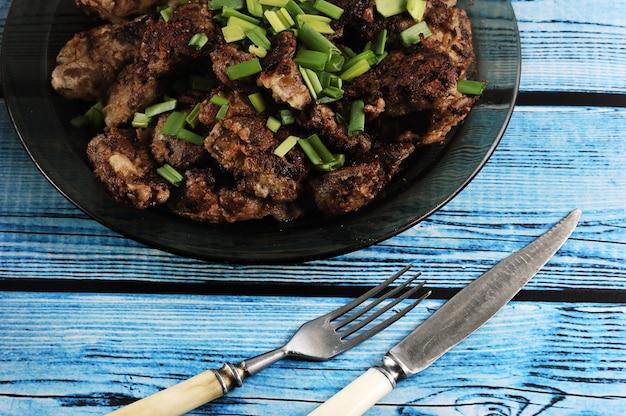 Fígado frito com cebola em um prato sobre um fundo azul