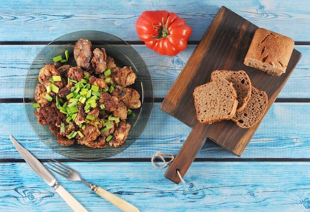 Fígado frito com cebola em um prato, tomate e pão de centeio