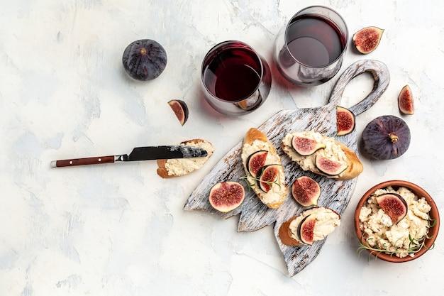 Figo, sanduíches de cream cheese com vinho tinto. petiscos de antepastos e vinho tinto em taças. banner, menu, local de receita para texto, vista superior.