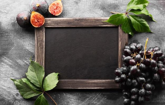 Figo, uvas, folhas e quadro-negro