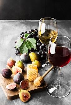 Figo, uvas, pão, mel e vinho tinto e branco
