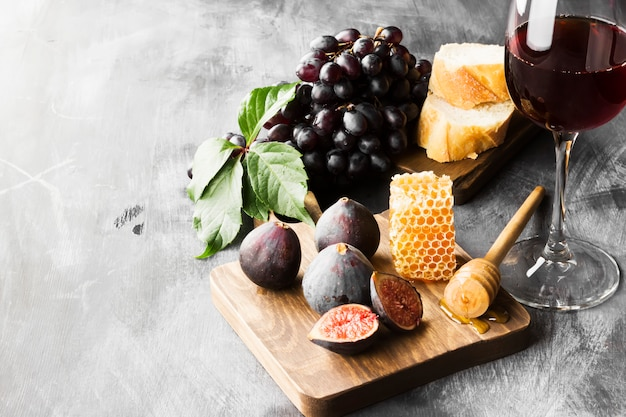 Figo, uvas, pão, mel e vinho tinto