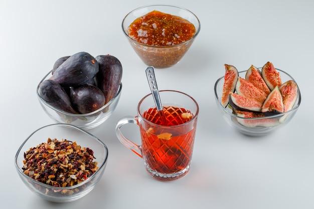 Figos com geléia de figo, chá, colher de chá, ervas secas em tigelas em branco, vista de alto ângulo.
