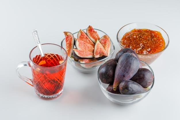 Figos com geléia de figo, xícara de chá, colher de chá em tigelas em branco, vista de alto ângulo.