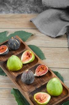 Figos com sementes vermelhas em uma bandeja de madeira.