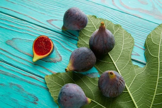 Figos cru frutas cortadas e folhas de figueira em azul