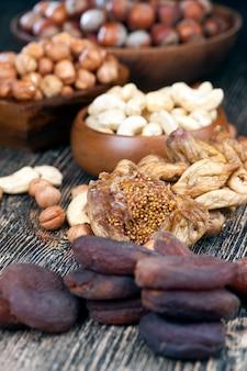 Figos doces secos e outras nozes e frutas secas, figos naturais junto com avelãs, castanhas de caju sobre uma mesa de madeira, ao lado de um damasco seco, tudo natural e seco ao sol