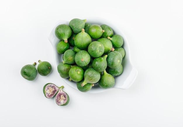 Figos e fatias em um prato deitado em uma parede branca