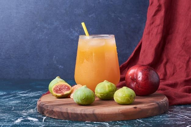 Figos e pêssego com um copo de bebida em azul.