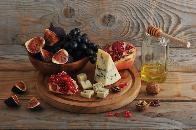 Figos e uvas pretas em uma tigela de madeira