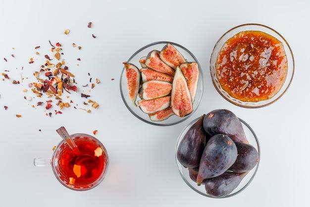 Figos em tigelas com geléia de figo, chá, colher de chá, ervas secas planas leigos em um branco