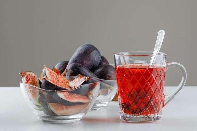 Figos em tigelas com uma xícara de chá, colher de chá vista lateral em branco e cinza