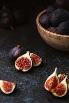 Figos fatiados na mesa e frutas maduras em uma tigela de madeira