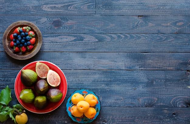 Figos frescos com morangos de mirtilos damascos pêssegos em um fundo de madeira.
