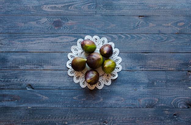 Figos frescos com pêssegos, damascos, mirtilos, morangos, sobre um fundo de madeira.