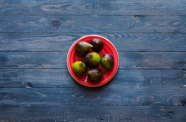 Figos frescos com pêssegos, damascos, mirtilos, morangos, sobre uma mesa de madeira
