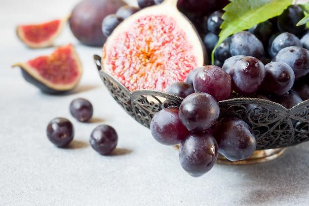 Figos frescos e uvas pretas com folhas em uma placa em um foco seletivo da tabela cinzenta. copie espaço