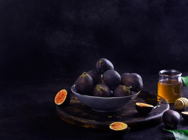 Figos frescos em uma mesa de madeira escura com mel com espaço de cópia